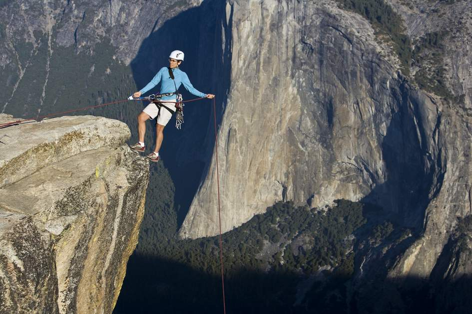Climber on the summit of a rock monolith in Yosemite National Park, California