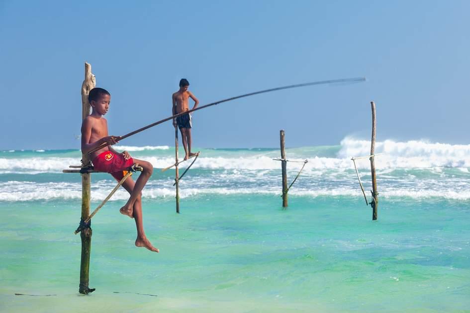 Young stilt fishermen at Hikkaduwa Beach, Sri Lanka
