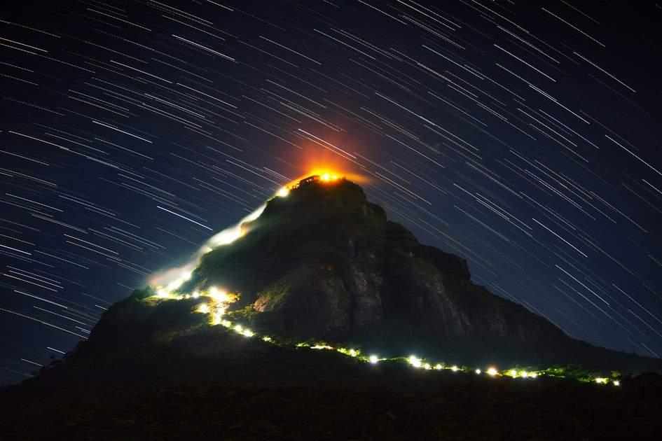 Mountain Adam's Peak (Sri Pada) illuminated at night with starry sky on the background. Sri Lanka