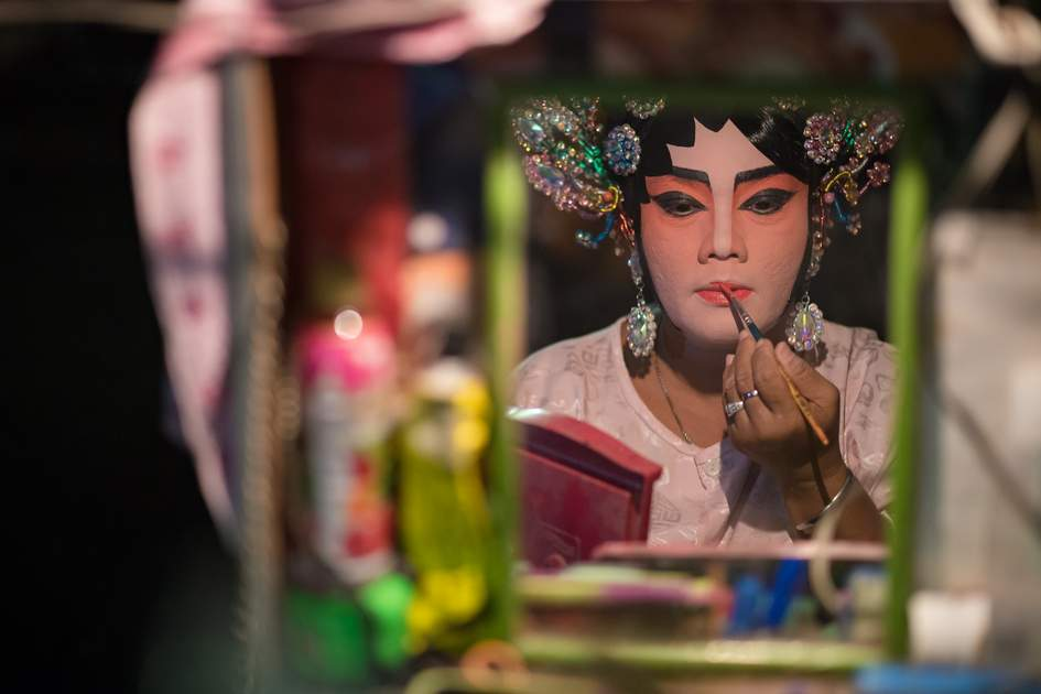 A Chinese opera actress painting mask on her face before the performance at backstage at major shrine in Bangkok's chinatown on October 16, 2015 in Bangkok,Thailand