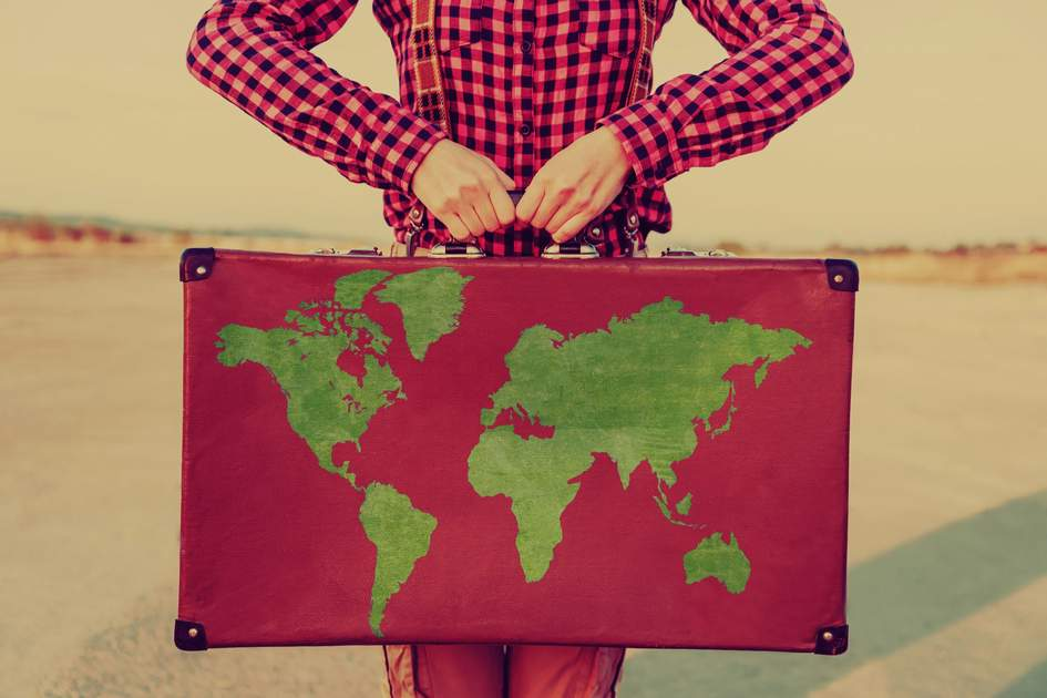 Traveler woman holding a suitcase with map of world
