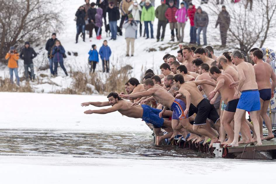 Sofia, Bulgaria: Men jump into freezing lake waters for a wooden cross at Epiphany day celebration.