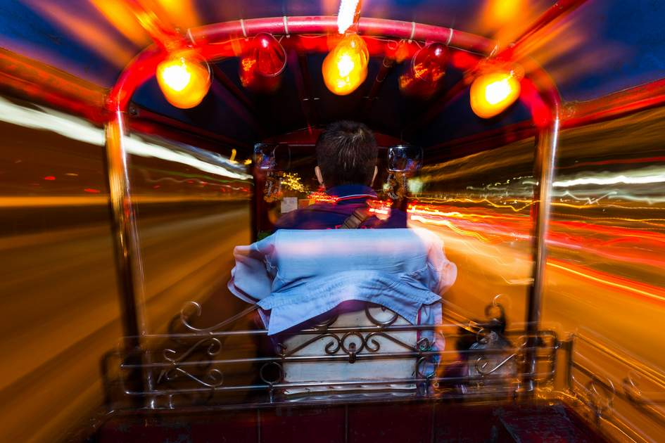 Dynamic perspective and long time exposure inside a Tuk tuk vehicle in Bangkok