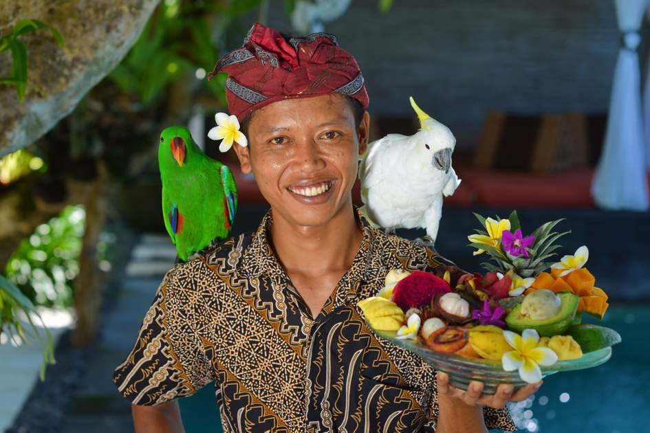 Indonesian waiter with a tray of tropical fruits. Shoot in a luxury resort on Bali island, Indonesia.