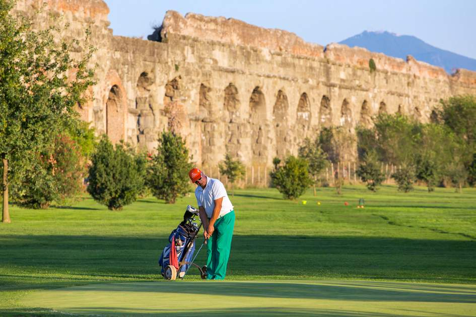 Unidentified man playing golf at the golf course next to the Ancient Roman Aqueduct in Parco degli Acquedotti. Famous Aqua Claudia Aqueduct is around 2000 years old.