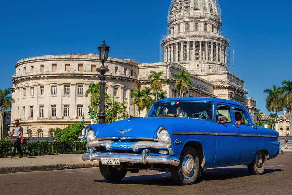 An old classic American blue car on the background of National Capitol Building in Havana