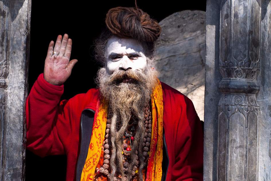 Unidentified Holy Sadhu men with traditional painted face, blessing in Pashupatinath Temple, Kathmandu. Photo: Shutterstock