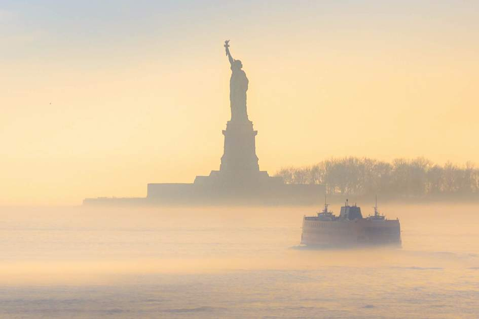 Staten Island Ferry cruises past the Statue of Liberty on a misty morning. Photo: Shutterstock