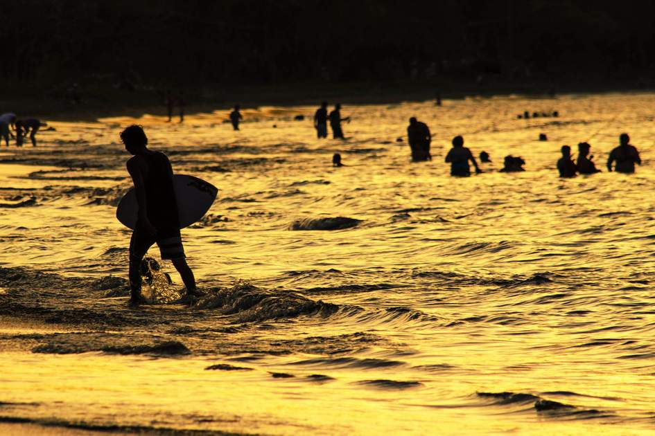 Surfers at sunset on Coco Beach, Costa Rica