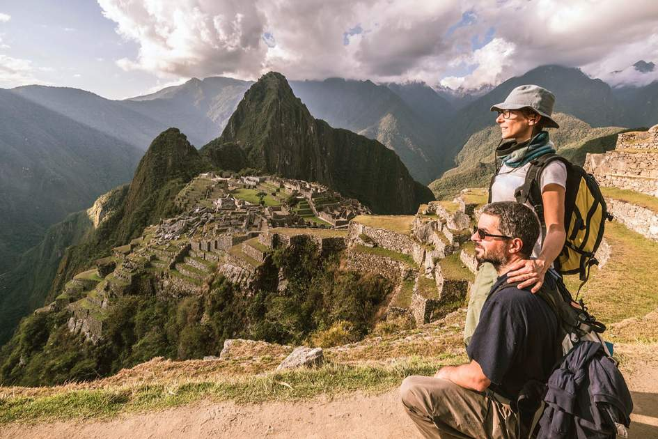 Hugging couple standing in contemplation on the terraces above Machu Picchu. Photo: Shutterstock