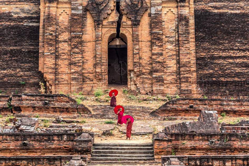 Three Buddhist novice are walking and holding the red umbrella at Mingun Pahtodawgyi, bagan