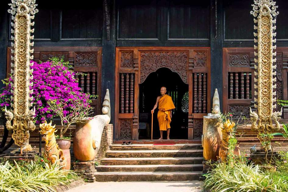 Old monk standing on the doorsteps of an ancient temple in Chiang Mai. Photo: Shutterstock