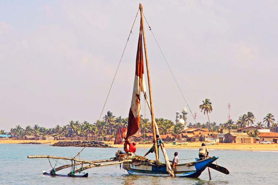 A traditional Sri Lankan fishing boat and fishermen on the water at Negombo. Photo: Shutterstock