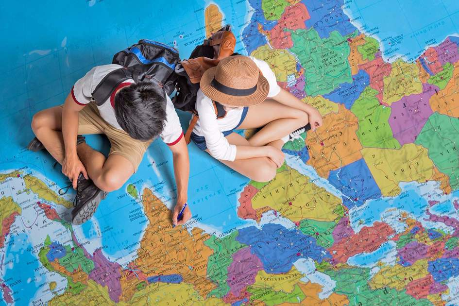 Travellers sat on a world map