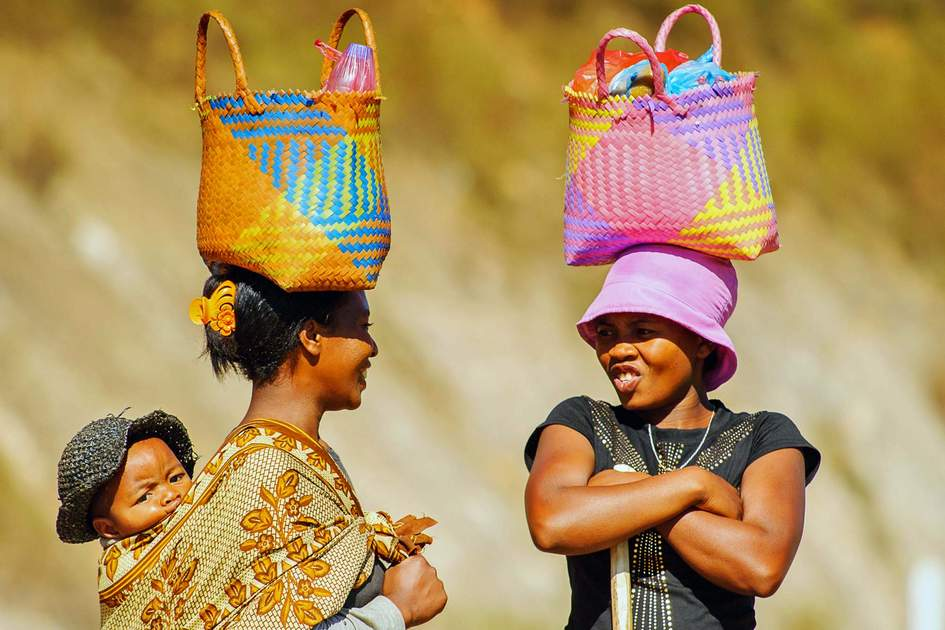 Unidentified Madagascar women walk and carry bags on their heads and a baby on a back.