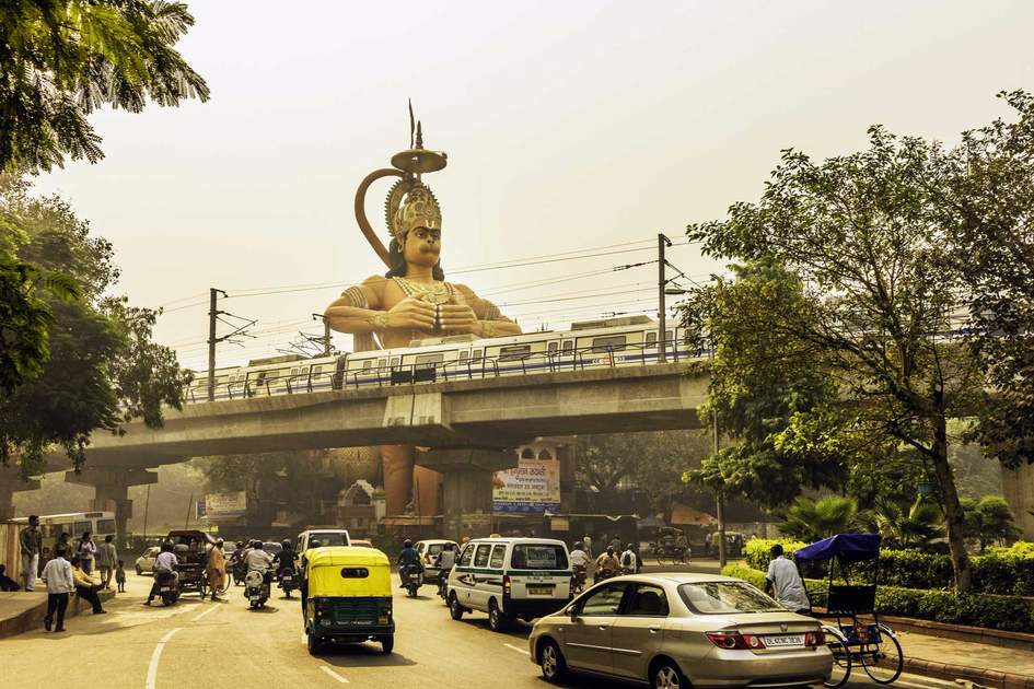 View of the giant Hanuman, Monkey God, temple overlooking the Metro and traffic at Karol Bagh, New Delhi, India.
