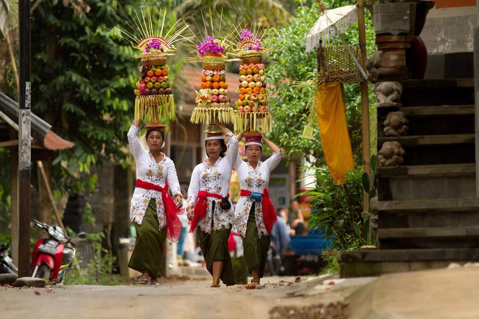 Villagers carrying food offerings on their heads, Bali
