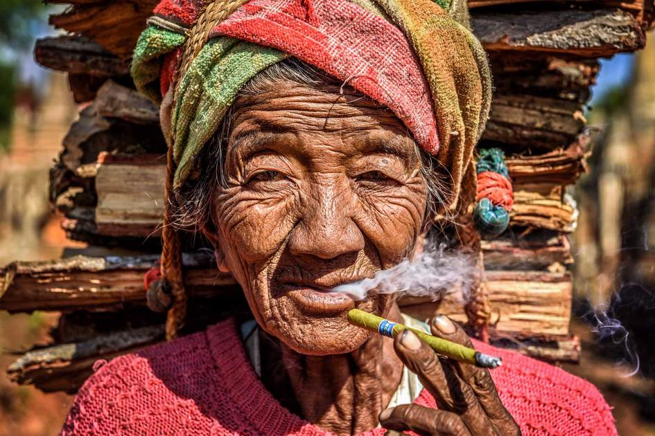 IN DEIN, MYANMAR: old wrinkled woman smokes a cheroot cigar