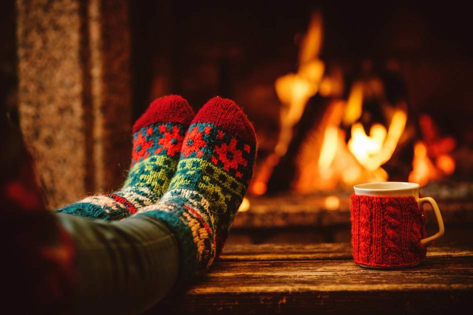Relaxing by warm fire with a cup of hot drink. Photo: Shutterstock