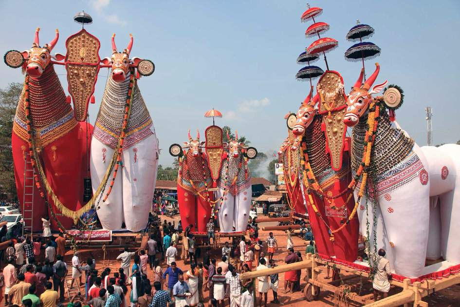 Devotees look at the massive bullock effigies displayed during the Shivratrhri festival at Padanilam Parabrahma temple on February 18,2015 in Nooranad,Kerala, India
