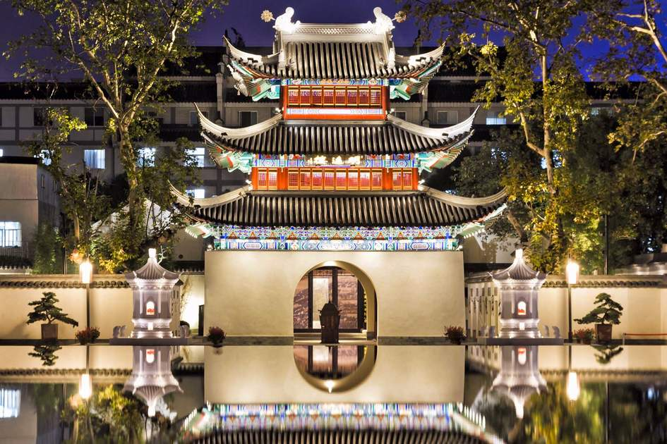 Ancient confucius temple in Chinese city Nanjing illuminated at sunset with still reflection of facade in waterpool