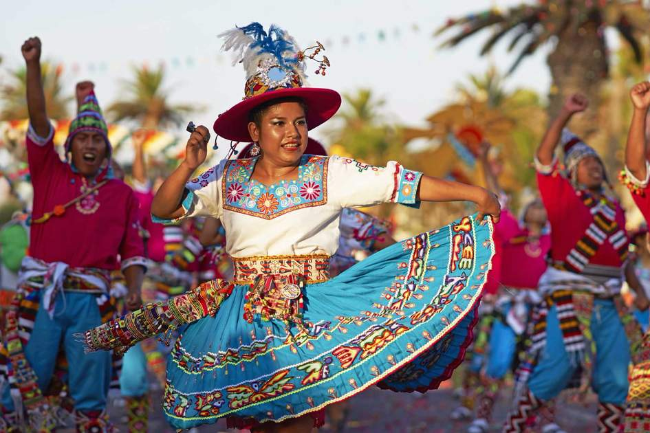 Tinku dancing group in colourful costumes performing a traditional ritual dance as part of the Carnaval Andino con la Fuerza del Sol in Arica, Chile.
