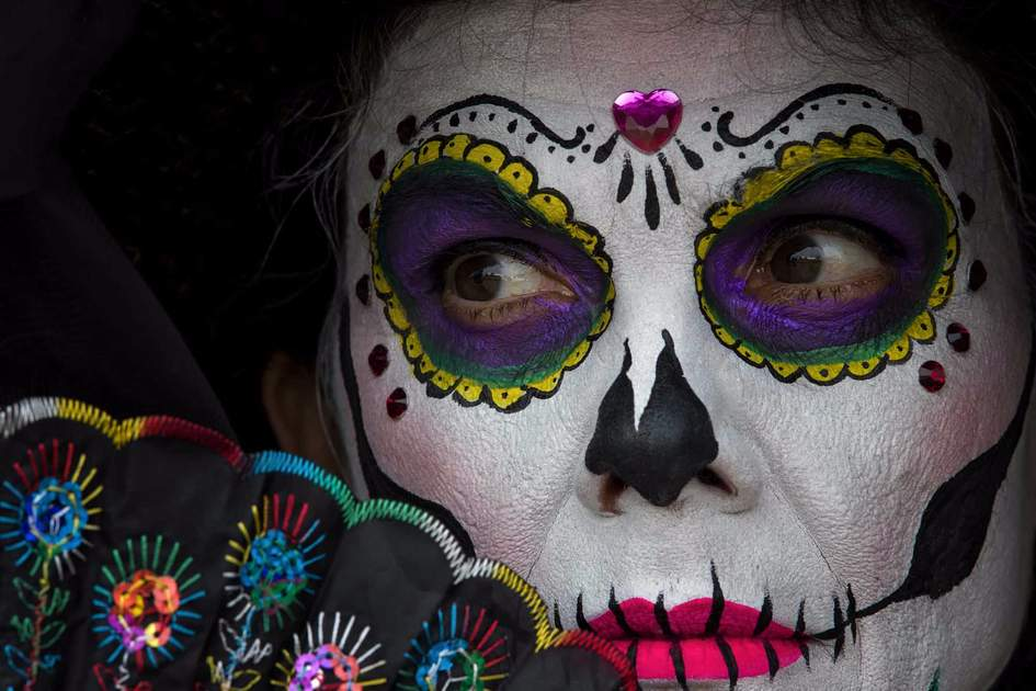 Attractive woman with colorful skull makeup and hand fan. Mexican Day of the dead Catrina woman wearing skull makeup for spooky celebration.