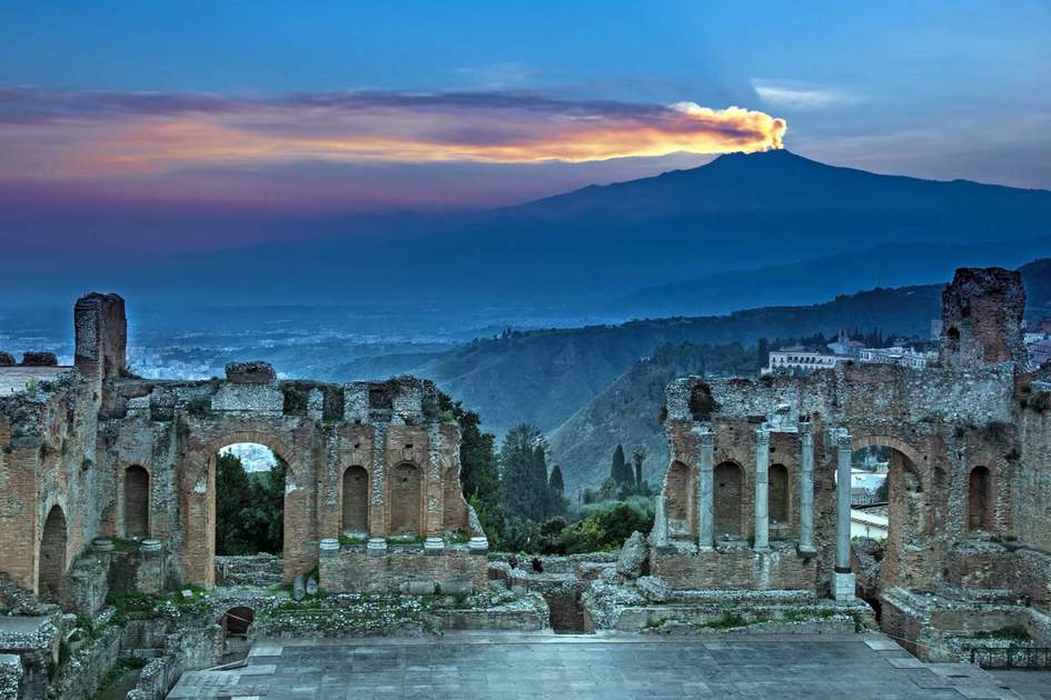 The ruins of the amphitheater on background Etna at sunset
