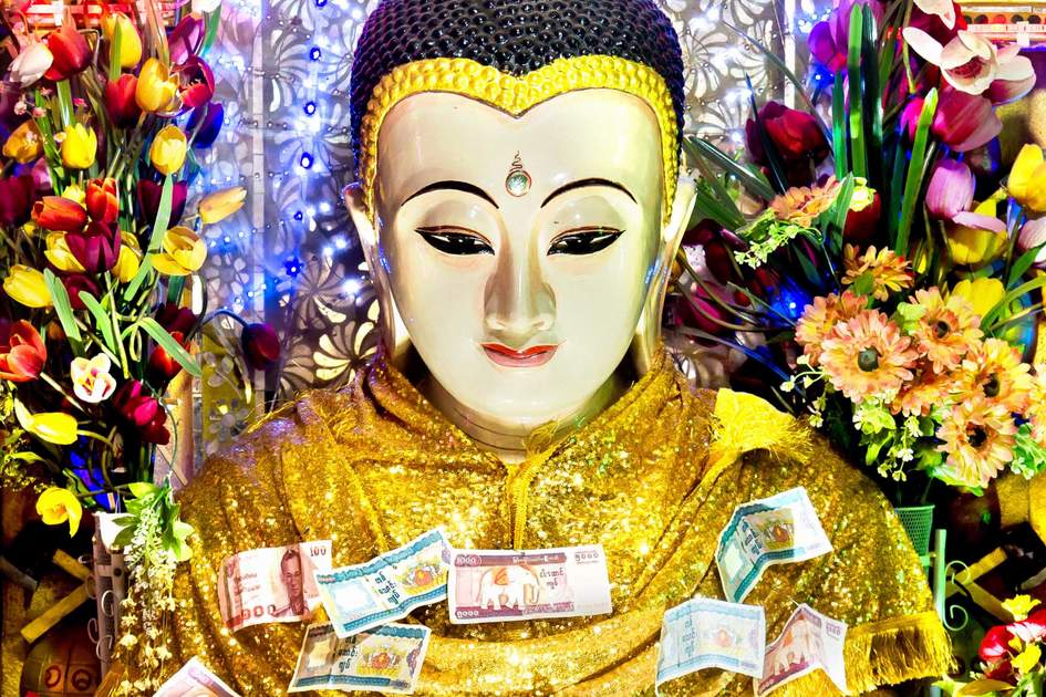 Revered Buddha statue with money and flower offerings from pilgrims at Mount Popa, Bagan, Myanmar