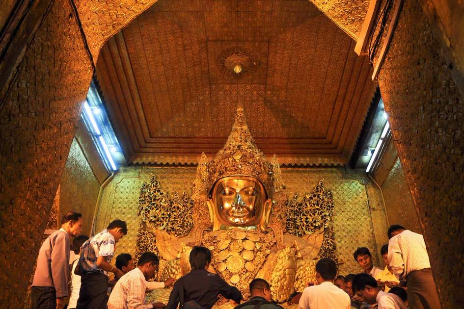 The Myanmar people pay respect to Mahamuni Buddha statue with the golden paper at Mahamuni Buddha temple.