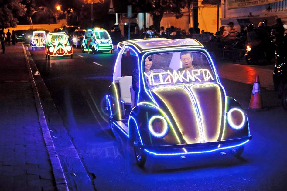 Undefined residents and tourists having fun riding on the illuminated pedal toy cars at night in Yogyakarta,  Indonesia