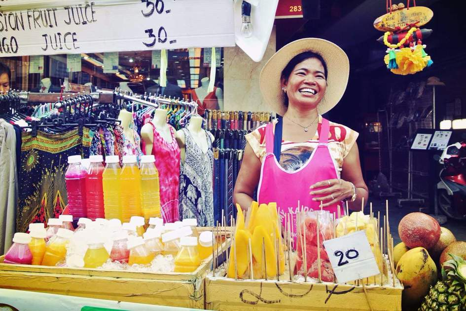 Laughing woman sells fresh fruit in Bangkok. Photo: Shutterstock