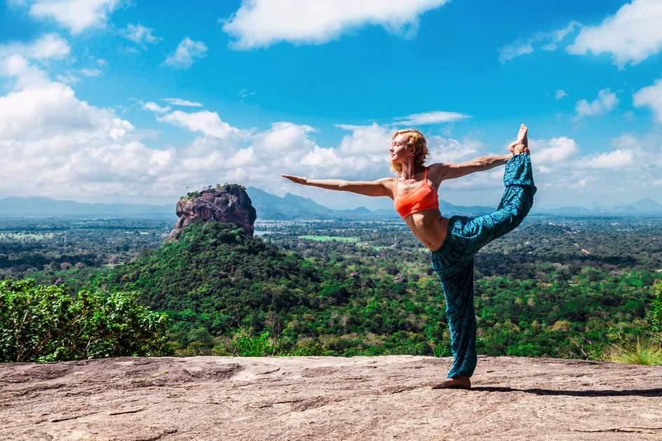 Young woman makes yoga pose on the mountain Pidurangala Rock, Sigiriya, Sri Lanka. Photo: Shutterstock