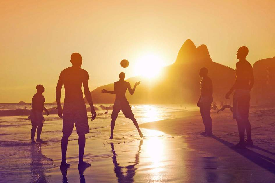 Silhouette of locals playing ball game at sunset in Ipanema beach, Rio de Janeiro. Photo: Shutterstock