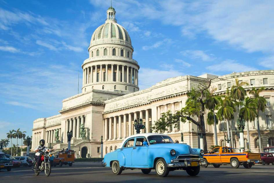 Classic American cars serving as taxis in front of the Capitolio building in Central Havana. Photo: Shutterstock
