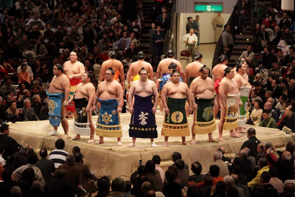 High rank sumo wrestlers line up with crowd in the Tokyo Grand Sumo Tournament. Photo: Shutterstock