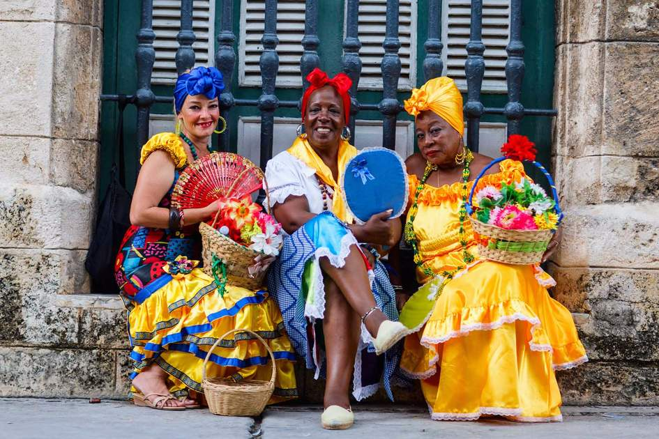 Cuban women in traditional clothing and carrying baskets of flowers in Old Havana. Photo: Shutterstock