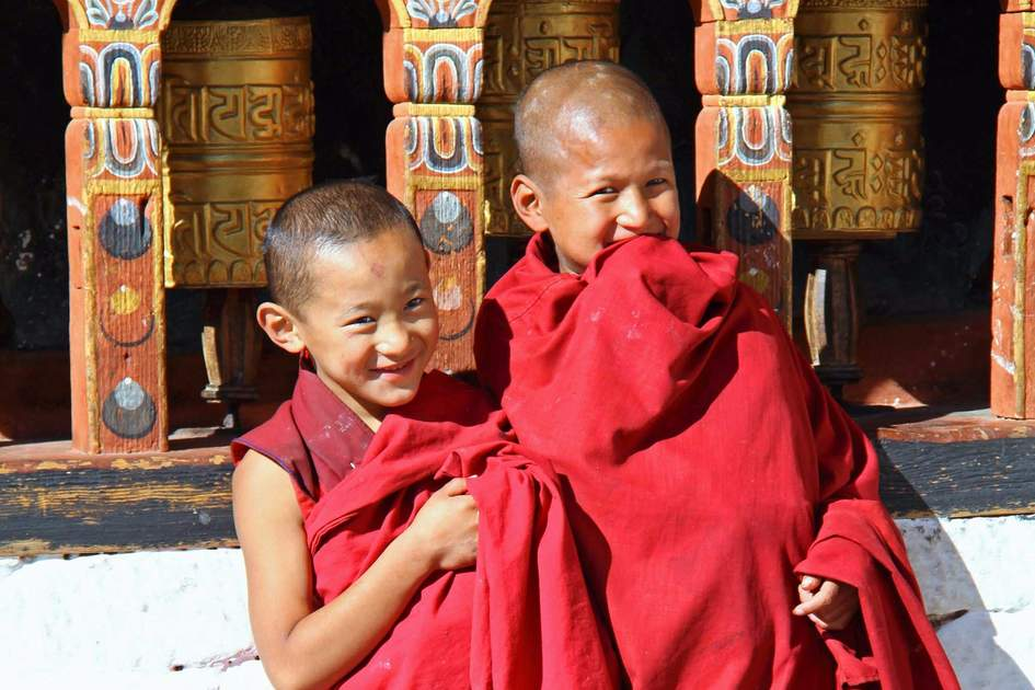 Young monks standing by the religious prayer wheels at Paro Rinpung dzong, Paro, Bhutan. Photo: Shutterstock