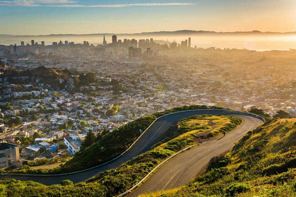Curvy road and view of downtown at sunrise from Twin Peaks, in San Francisco. Photo: Shutterstock