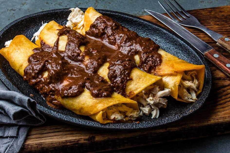 Mexican chicken enchiladas with spicy chocolate salsa mole poblano. Photo: Larsa Blinova/Shutterstock