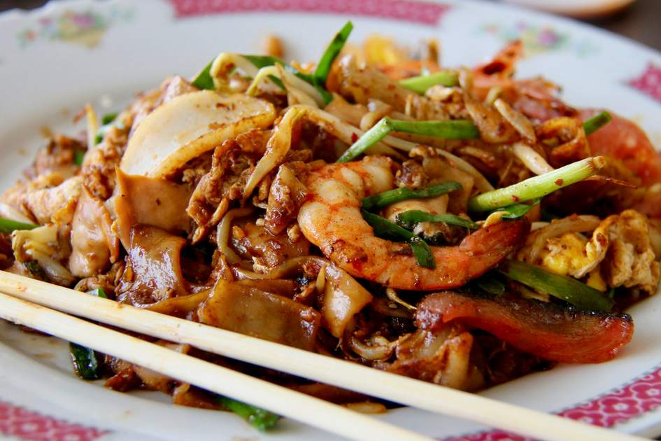 Enjoy char kway teow – a favorite Singapore street food dish with stir-fried rice noodles, seafood, and beansprouts, on a trip to the vibrant island city state. Photo: Ariyani Tedjo/Shutterstock