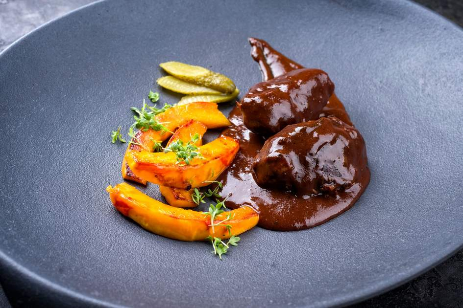 Ox cheeks in brown red wine sauce with pumpkin slices and herbs. Photo: hlphoto/Shutterstock